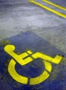 Image shows a parking stall with a painted wheelchair user indicating that it is reserved for people who have physical disabilities.